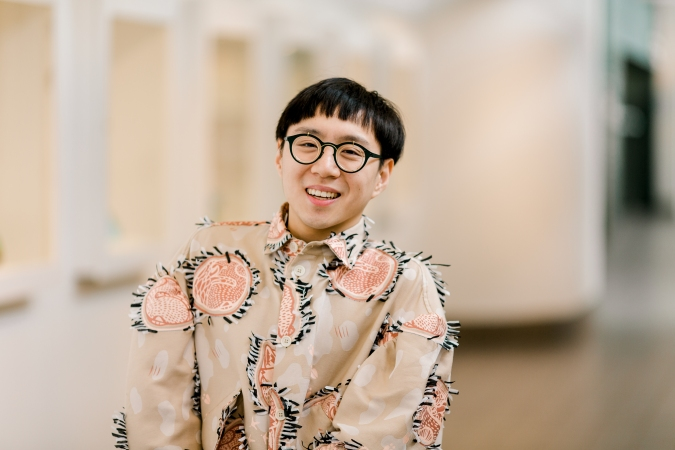 A photo of Sean Lee, a disabled, Asian and queer artist, smiling at the camera. He is wearing a beige dress punctuated by small red frilly circles with textiles of sleeping animals.